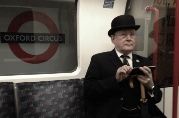 A man in bowler hat and 3-piece suit on the Tube using a smart phone.