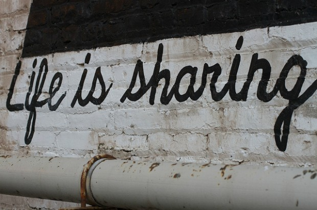A mural on a brick wall saying 'Life is sharing'.